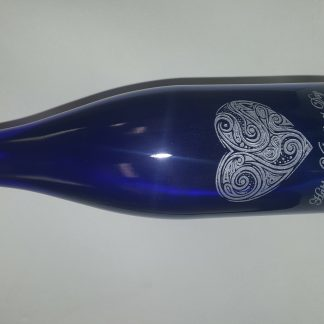 "laser engraved wine bottle with a heart shaped graphic. The words ""Happy Valentines Day 2017"" are also engraved on the bottle."